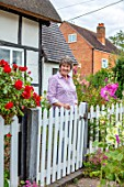 THATCH COTTAGE, WORCESTERSHIRE: OWNER MARY COX AT THE WHITE FRONT GATE OF HER COTTAGE