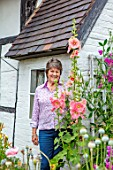 THATCH COTTAGE, WORCESTERSHIRE: OWNER MARY COX SURROUNDED BY TALL HOLLYHOCKS