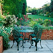FORMAL GARDEN: FLAGSTONE PATIO WITH TABLE & CHAIRS BESIDE BED OF ROSES & VALERIAN. DESIGNER: JILL BILLINGTON