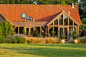 TYGER BARN, NORFOLK: DESIGNER JULIANNE FERNANDEZ: THE BARN FROM THE LAWN, JULY, STIPA TENUISSIMA, ENGLISH, COUNTRY, GARDEN