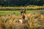 TYGER BARN, NORFOLK: DESIGNER JULIANNE FERNANDEZ: TERRACE, STIPA TENUISSIMA, AGAPANTHUS, SCULPTURE OF DEER BY BLACK COUNTRY IRONWORKS