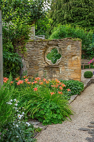 ADAMS_POOL_GLOUCESTERSHIRE_HEMEROCALLIS_PATH_FOLLY_WALL_WITH_QUATREFOIL_RECYCLED_CHURCH_WINDOW