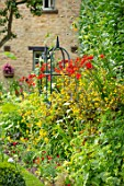 ADAMS POOL, GLOUCESTERSHIRE: HOT, RED BORDER BY LAWN, BORDER, COTTAGE, GARDEN, COTSWOLDS, CROCOSMIA LUCIFER, SEDUMS, LYSIMACHIA