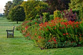 GLYNDEBOURNE, EAST SUSSEX: LAWN, BORDER, OPERA HOUSE. CROCOSMIA HELLFIRE, CROCOSMIA LUCIFER, DAHLIA BISHOP OF LLANDAFF, SALVIA ROYAL BUMBLE, RED BORDERS, ENGLISH, COUNTRY, GARDEN