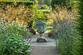 GLYNDEBOURNE, EAST SUSSEX: PATH, BORDERS, URN, STONE CONTAINER PLANTED WITH DICHONDRA SILVER FALLS, STIPA GIGANTEA, VERBENA BONARIENSIS, AMMI VISNAGNA