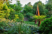 GLYNDEBOURNE, EAST SUSSEX: LAWN, CORTEN STEEL METAL SCULPTURE BY NICHOLAS HARE, DICKSONIA ANTARCTICA, HOSTA SIEBOLDIANA,