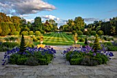 PRIVATE GARDEN, GLOUCESTERSHIRE - DESIGNER ANGEL COLLINS: TERRACE WITH AGAPANTHUS NAVY BLUE, GRASS WALK TO LAKE AND FOUNTAIN