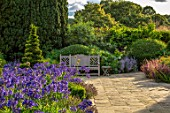 PRIVATE GARDEN, GLOUCESTERSHIRE - DESIGNER ANGEL COLLINS: TERRACE WITH AGAPANTHUS NAVY BLUE, WOODEN BENCH, SEAT, SEATING, BENCHES, AUGUST