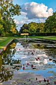 PRIVATE GARDEN, GLOUCESTERSHIRE - DESIGNER ANGEL COLLINS: VIEW ACROSS THE WATERLILIES IN LAKE TO FOUNTAIN, AUGUST, EVENING