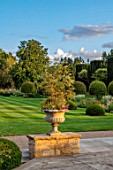 PRIVATE GARDEN, GLOUCESTERSHIRE - DESIGNER ANGEL COLLINS: TERRACE, URN, CONTAINER LOOKING OUT TO PARKLAND, AUGUST