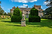 CANONS ASHBY, NORTHAMPTONSHIRE, THE NATIONAL TRUST: GREEN COURT, THE HOUSE, YEW TOPIARY, LEAD STATUE OF SHEPHERD BOY FROM A MODEL BY JAN VON NOST
