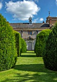 CANONS ASHBY, NORTHAMPTONSHIRE, THE NATIONAL TRUST: GREEN COURT,  THE WEST FRONT, DOOR, COAT OF ARMS CAST IN LEAD, YEW TOPIARY