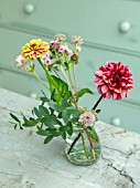 GREEN AND GORGEOUS FLOWERS, OXFORDSHIRE: TABLE ARRANGEMENT OF GLASS VASE FOR WEDDING ALONG GREY, BLUE TABLE - DAHLIAS, ZINNIAS, EUCALYPTUS, FALL, AUTUMN, BLOOMING, BULBS
