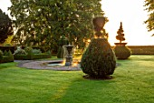 MITTON MANOR, STAFFORDSHIRE: FOUNTAIN AND CLIPPED YEW TOPIARY IN THE FRONT GARDEN. FOUNTAIN, POOL, FORMAL, LAWN, SUNRISE, COUNTRY, GARDEN, ENGLISH, LAWN, WATER