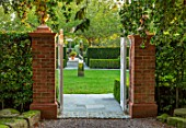 MITTON MANOR, SHROPSHIRE: VIEW THROUGH WHITE WOODEN GATES TO DAVID HARBER SUNDIAL IN LAWN