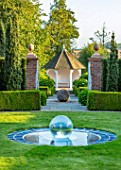 MITTON MANOR, SHROPSHIRE: VIEW ACROSS THE AQUA LENS GARDEN TO PAVILION THROUGH GATES. LAWN, WATER FEATURE, FOUNTAIN, BALL, SEPTEMBER