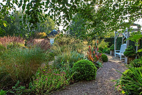MITTON_MANOR_SHROPSHIRE_THE_ROUNDHOUSE_GARDEN__WOODEN_PERGOLA_SEAT_BENCH_PATH_BOX_TOPIARY_IN_WOODEN_