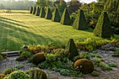 ROCKCLIFFE GARDEN, GLOUCESTERSHIRE: VIEW ACROSS LAWN AT SUNRISE WITH TERRACE, CLIPPED BEECH OBELISKS, BORROWED LANDSCAPE, BRONZE SCULPTURE SOUTHERN SHADE BY NIGEL HALL