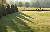 ROCKCLIFFE GARDEN, GLOUCESTERSHIRE: VIEW ACROSS LAWN AT SUNRISE, CLIPPED BEECH OBELISKS, BORROWED LANDSCAPE, BRONZE SCULPTURE SOUTHERN SHADE BY NIGEL HALL, SHADOWS