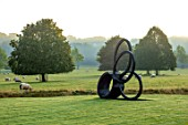 ROCKCLIFFE GARDEN, GLOUCESTERSHIRE: VIEW ACROSS LAWN AT SUNRISE WITH BORROWED LANDSCAPE, BRONZE SCULPTURE SOUTHERN SHADE BY NIGEL HALL