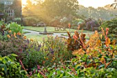 GRAVETYE MANOR, SUSSEX: MORNING LIGHT, LAWN, BORDERS, SEPTEMBER, DAHLIA DAVID HOWARD, SALVIA CONFERTIFLORA, CANNAS, SALVIA AMISTAD, FUCHSIA, SUNRISE, MIST, FOG