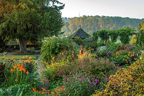 GRAVETYE_MANOR_SUSSEX_MORNING_LIGHT_LAWN_BORDERS_SEPTEMBER_DAHLIA_DAVID_HOWARD_CANNAS_DAHLIA_MAGENTA
