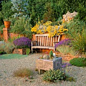 GRAVEL GARDEN:FRAGRANT BENCH IN BRICK ALCOVE SURROUNDED BY LAVENDER  HELICHRYSUM & AGAVES IN POTS. THE OLD VICARAGE  NORFOLK.