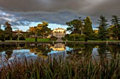 THORP PERROW ARBORETUM, YORKSHIRE: THE VIEW OF THE HOUSE ACROSS THE LAKE IN AUTUMN. TREES, LAKES, WATER, EVENING LIGHT, REFLECTIONS, REFLECTED