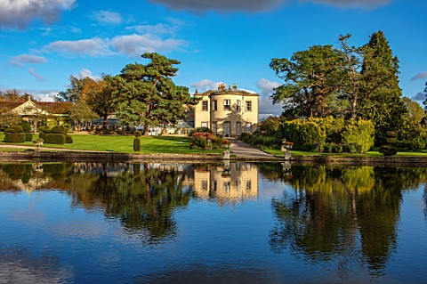 THORP_PERROW_ARBORETUM_YORKSHIRE_CLIPPED_TOPIARY_YEW_HOUSE_ACROSS_THE_LAKE_IN_AUTUMN_TREES_LAKES_WAT