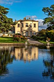 THORP PERROW ARBORETUM, YORKSHIRE: HOUSE ACROSS THE LAKE IN AUTUMN. TREES, LAKES, WATER, EVENING LIGHT, REFLECTIONS, REFLECTED