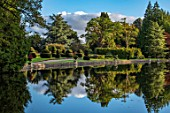 THORP PERROW ARBORETUM, YORKSHIRE: CLIPPED TOPIARY YEW, HOUSE ACROSS THE LAKE IN AUTUMN. TREES, LAKES, WATER, EVENING LIGHT, REFLECTIONS, REFLECTED