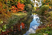 THORP PERROW ARBORETUM, YORKSHIRE: POOL, POND, LAKE WITH HERON SCULPTURE AND AUTUMN COLOUR OF JAPANESE MAPLES, ACERS, FALL