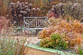 THE OLD RECTORY, QUINTON, NORTHAMPTONSHIRE: DESIGNER ANOUSHKA FEILER: GRASSES, AUTUMN, FALL, WOODEN BENCH, SEAT, FROST, FROSTY, EUPHORBIA WALLICHII