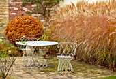 THE OLD RECTORY, QUINTON, NORTHAMPTONSHIRE: DESIGNER ANOUSHKA FEILER: TABLE, CHAIRS, MISCANTHUS SINENSIS KLEINE FONTAINE, PATIOS, AUTUMN, FALL, FAGUS SYLVATICA