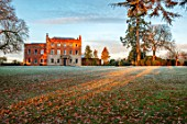 MORTON HALL GARDENS, WORCESTERSHIRE: THE HALL, LAWN, FROST, WINTER, SUNRISE, GRASS, FALLEN, LEAVES