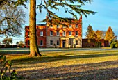 MORTON HALL GARDENS, WORCESTERSHIRE: THE HALL, LAWN, WINTER, SUNRISE, GRASS, FALLEN, LEAVES
