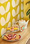 RACHEL HENDERSON HOUSE, EDINBURGH, SCOTLAND: LIVING ROOM - BRIGHT WALLPAPER, TEA AND CUPCAKES ON SIDEBOARD