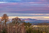 MORTON HALL GARDENS, WORCESTERSHIRE: VIEW TO MALVERN HILLS AT DAWN. SUNRISE, WINTER, JANUARY, LANDSCAPE