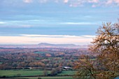 MORTON HALL GARDENS, WORCESTERSHIRE: VIEW TO ABBERLEY HILLS AT DAWN. SUNRISE, WINTER, JANUARY, LANDSCAPE