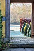 BRYANS GROUND, HEREFORDSHIRE: THE DOVECOTE GARDEN, BUILDING, DOORWAY, CLIPPED YEW TOPIARY OBELISKS, VIEW OUT TO COUNTRYSIDE, ENGLISH, GARDEN, BEECH, HEDGES, HEDGING, FROSTY