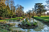 EYTHROPE, WADDESDON, BUCKINGHAMSHIRE: BRIDGE, LAKE, SNOWDROP ISLAND, URN, CONTAINER, PARKLAND, TREES, WATER, WINTER, JANUARY, GALANTHUS