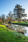 EYTHROPE, WADDESDON, BUCKINGHAMSHIRE: LAKE, SNOWDROPS, PARKLAND, TREES, WATER, WINTER, JANUARY, GALANTHUS, REFLECTIONS, REFLECTED