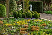 MORTON HALL GARDENS, WORCESTERSHIRE: YELLOW FLOWERS OF EPIMEDIUM X VERSICOLOR SULPHUREUM, WHITE AND PURPLE FLOWERS OF ANEMONE BLANDA, BOX TOPIARY, STATUE, PERENNIALS, SHADE, SHADY