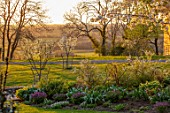 MORTON HALL GARDENS, WORCESTERSHIRE: WEST GARDEN SPRING, APRIL, WHITE FLOWERS OF SPIRAEA ARGUTA, BORDERS, SUNSET, EVENING