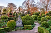 THE LASKETT GARDENS, HEREFORDSHIRE. DESIGNER ROY STRONG - THE SERPENTINE WALK - STATUE OF BRITANNIA, PATHS, CLIPPED, TOPIARY, BOX, HOLLY, ILEX, BUXUS, ACER GRISEUM, SPRING, APRIL