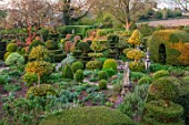 THE LASKETT GARDENS, HEREFORDSHIRE. DESIGNER ROY STRONG - THE SERPENTINE WALK - MAGNOLIA, ACER GRISEUM, PATHS, CLIPPED, TOPIARY, BOX, HOLLY, ILEX, BUXUS, SPRING, APRIL, YEW HEDGING