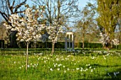 MORTON HALL GARDENS, WORCESTERSHIRE: THE MEADOW, PARK, SPRING, APRIL, MONOPTEROS, FOLLY, FOLLIES, DAFFODILS, NARCISSUS, CHERRIES, PRUNUS FRAGRANT CLOUD