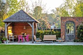 LITTLE ORCHARDS, SURREY, DESIGNER NIC HOWARD: SHED, OUTBUILDING, TABLE, PINK CHAIRS, PERGOLA, SEATING AREA, WALL, GOTHIC DOOR, DOORWAY, LAWN
