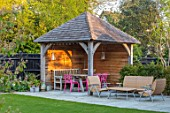 LITTLE ORCHARDS, SURREY, DESIGNER NIC HOWARD: SHED, OUTBUILDING, TABLE, PINK CHAIRS, PERGOLA, SEATING AREA, FENCES, FENCING, LAWN, LOUNGERS