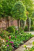 MORTON HALL GARDENS, WORCESTERSHIRE: THE SOUTH GARDEN, LAWN, BORDER WITH TULIPS, SPRING, APRIL, WALLED GARDENS, ARCH, SEAT, SEATING, BENCHES